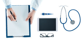 Doctor writing a prescription on a clipboard Royalty Free Stock Photography