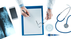 Doctor writing a prescription on a clipboard Stock Images