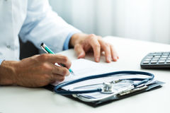 Doctor writing prescription at desk in clinics office Royalty Free Stock Images