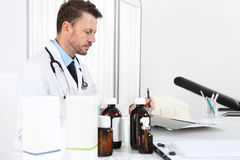 Doctor writing prescription at desk in medical office with drugs Royalty Free Stock Photo