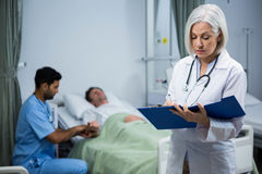 Doctor writing prescription in file. While surgeon consulting patient in background Stock Images