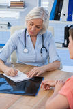 Doctor writing a prescription for her patient in medical office Royalty Free Stock Photos