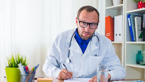Doctor writing a prescription. Doctor writing a prescription in his office Royalty Free Stock Images