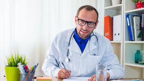 Doctor writing a prescription. Doctor writing a prescription in his office Stock Photo