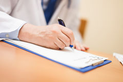 Doctor writing a prescription in his studio Royalty Free Stock Images