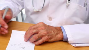 Doctor writing on prescription pad at his desk Stock Photo