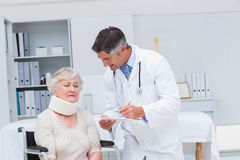 Doctor writing prescription for patient wearing neck brace Stock Images