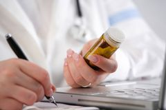Doctor writing a prescription with pills in her hand Royalty Free Stock Image