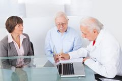 Doctor writing prescription for senior couple Stock Images
