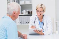 Doctor writing prescription for senior man Stock Photography