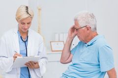 Doctor writing prescription for senior patient Stock Images