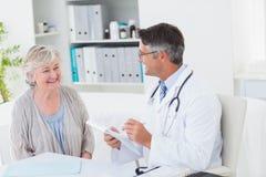Doctor writing prescriptions for senior female patient. Happy doctor writing prescriptions for senior female patient in clinic Stock Photo