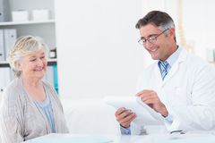 Doctor writing prescriptions for senior patient. Happy male doctor writing prescriptions for senior patient in clinic Stock Photos