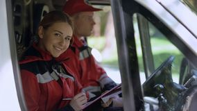 Doctor writing report in ambulance, smiling to camera, emergency medicine reform stock photos