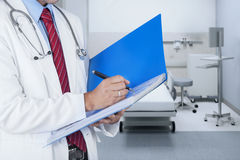 Doctor writing report on a folder. Male doctor writing medical report on a folder in hospital Stock Photography