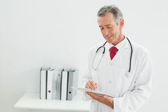 Doctor writing a report at the office Stock Photos