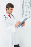 Doctor writing reports in the medical office Stock Images