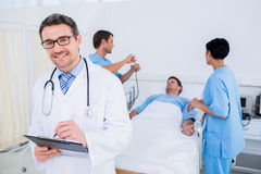 Doctor writing reports with patient and surgeons in background Royalty Free Stock Images
