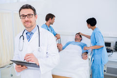 Doctor writing reports with patient and surgeons in background Stock Image