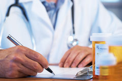 Doctor writing RX prescription stock photo