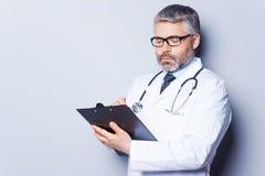 Doctor writing RX prescription. Stock Photos
