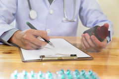 Doctor writing RX prescription in medical office clinic with dru Stock Image