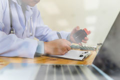 Doctor writing RX prescription in medical office clinic with dru Stock Photo