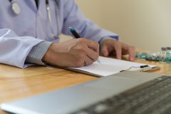 Doctor writing RX prescription in medical office clinic with dru Royalty Free Stock Photography