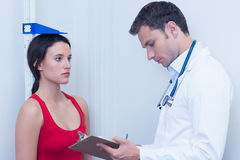 Doctor writing size of his patient on clipboard Stock Photo
