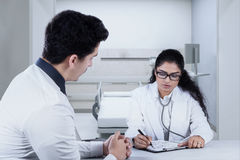 Doctor writing something for her patient Stock Photo