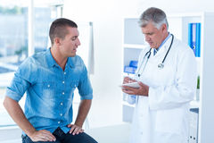 Doctor writing treatment for his patient stock photography