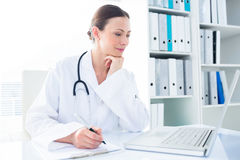 Doctor writing while using laptop. Beautiful female doctor writing while using laptop at desk in clinic Royalty Free Stock Images