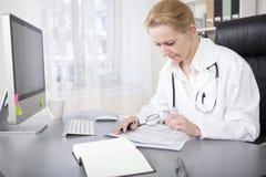 Doctor Writing y lectura de la mujer en su oficina Imagen de archivo libre de regalías