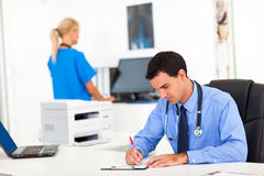 Doctor writingl report Stock Photo