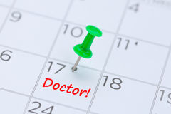 Doctor written on a calendar with a green push pin to remind you royalty free stock photos