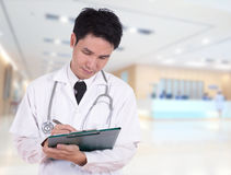 Doctor writting medical report Stock Image