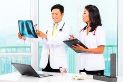 Doctor y enfermera asiáticos en cirugía Fotos de archivo libres de regalías