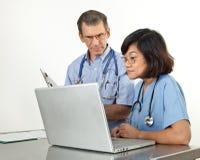 Doctor y enfermera en el ordenador portátil Fotos de archivo