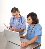 Doctor y enfermera en el ordenador portátil Imágenes de archivo libres de regalías