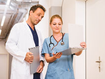 Doctor y enfermera que discuten cartas Fotos de archivo