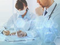 Doctor y enfermera que escriben informe del análisis químico Fotos de archivo