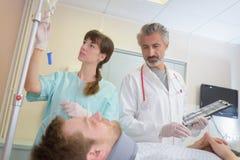 Doctor y enfermera que hablan con el paciente en cama fotografía de archivo libre de regalías