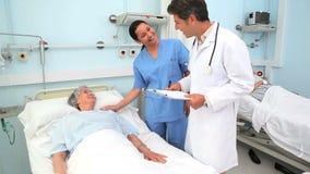 Doctor y enfermera que hablan con un paciente almacen de metraje de vídeo