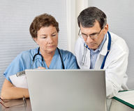 Doctor y enfermera que repasan en el ordenador portátil en O Imagen de archivo libre de regalías