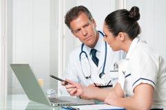 Doctor y enfermera que trabajan en la computadora portátil Foto de archivo libre de regalías