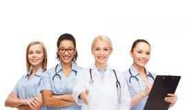Doctor y enfermeras de sexo femenino sonrientes con el estetoscopio Imagen de archivo libre de regalías