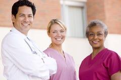 Doctor y enfermeras que se colocan fuera de un hospital Imágenes de archivo libres de regalías