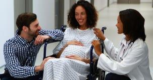 Doctor y hombre que obran recíprocamente con la mujer embarazada en pasillo metrajes