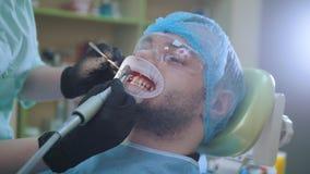 Doctor y paciente con el dilatador del labio en la oficina dental, puliendo con el cepillo metrajes