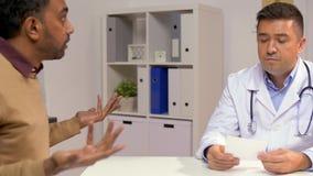 Doctor y paciente masculino descontentado en la clínica metrajes